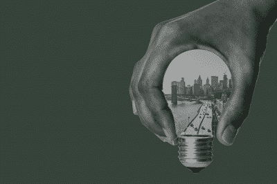 green background with hand holding lightbulb inlaid with eastern cityscape